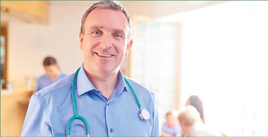Arzt in hellblauem Hemd, Sthoskop umgelegt, lächelt in die Kamera