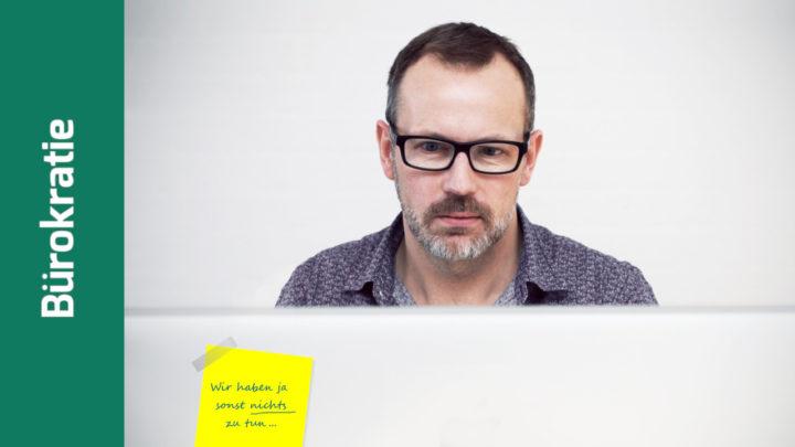 Mann sitzt hinter dem Laptop
