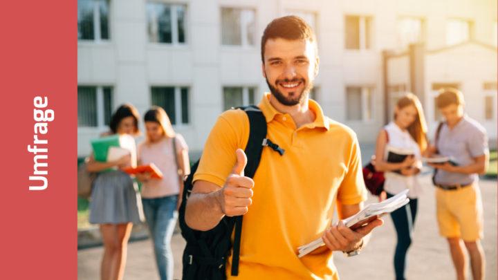 Junger lächelnder Mann vor Uni oder Uni-Klinik hält den Daumen hoch