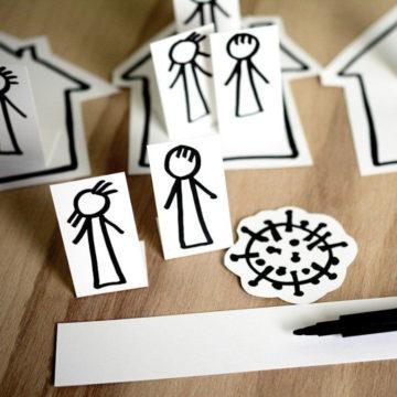 social distancing mit ausgeschnittenen Menschen und Häusern dargestellt
