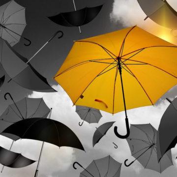 Ein gelber (Rettungs)Schirm am Himmel zwischen vielen grauen und schwarzen Schirmen