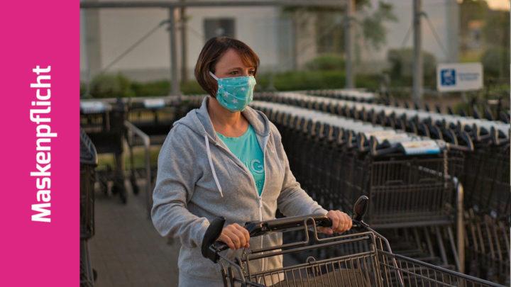 Frau mit Behelfsmaske schiebt einen Einkaufswagen