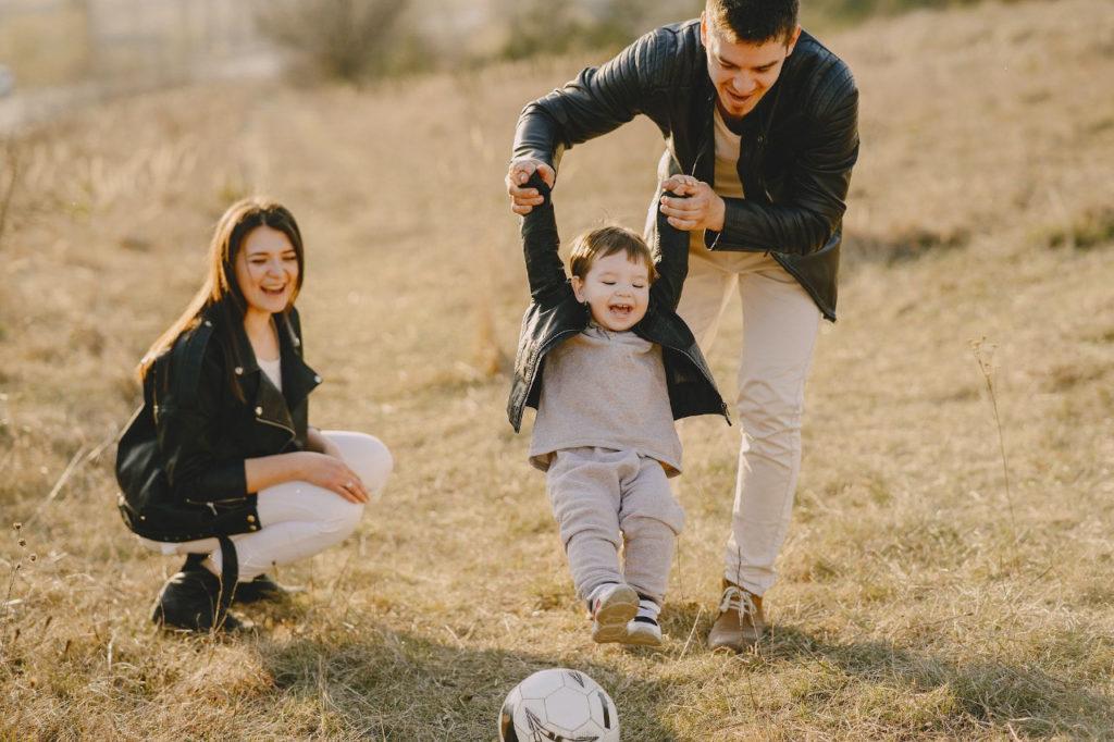 Diese Eltern haben Spaß. Der Vater schwenkt den Sohn im Kindergartenalter auf der Wiese nach vorne