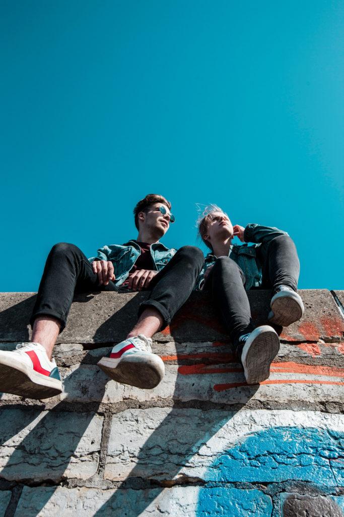 2 junge Männer sitzen auf einer Mauer. Aus der Froschperspektive fotografiert.