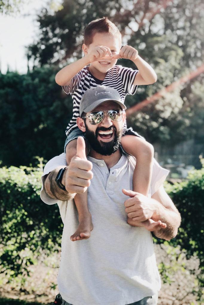Bärtiger Vater mit Sonnenbrille und Cap trägt seinen Sohn auf den Schultern und zeigt lachend den aufgestellten Daumen.