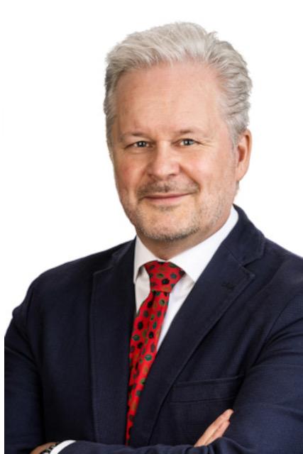 Portrait-Foto eines freundlich lächelnden, grauhaarigen Mannes im dunklen Anzug mit rotem Schlips an weißem Hemd