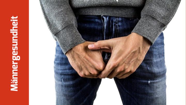 Ausschnitt eines Fotos von einem Mann in Pullover und Jeans, der sich die Hände vor die Genitale hält