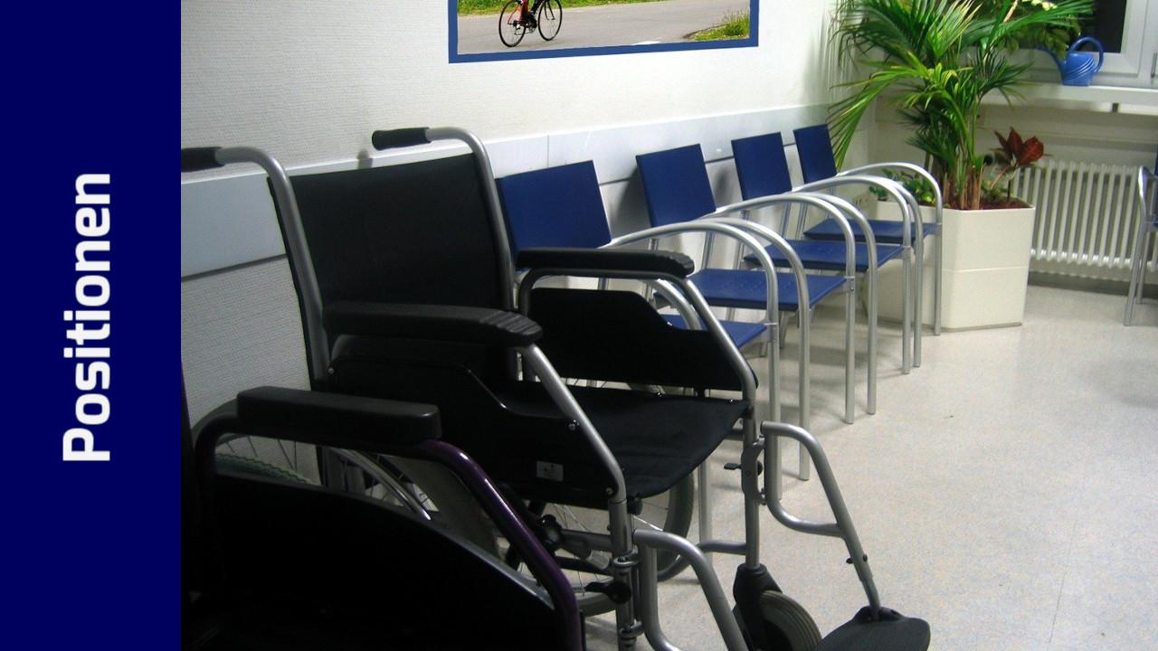 Ein leeres Wartezimmer mit einfachen Stühlen und Rollstühlen