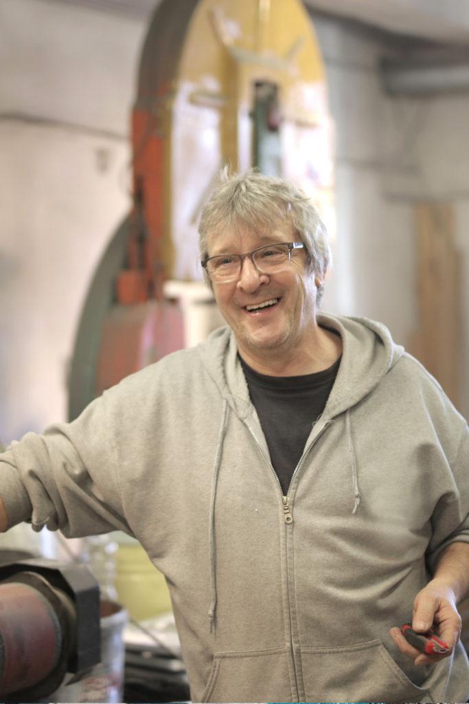 Mann mit Brille und wuseligen grauen Haaren in T-Shirt und Hoodie bei der Arbeit