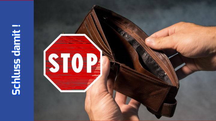 Hände halten ein leeres Portemonnaie. Davor ein gezeichnetes Stop-Schild.